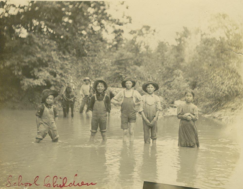 Potawatomi children wading in a pond