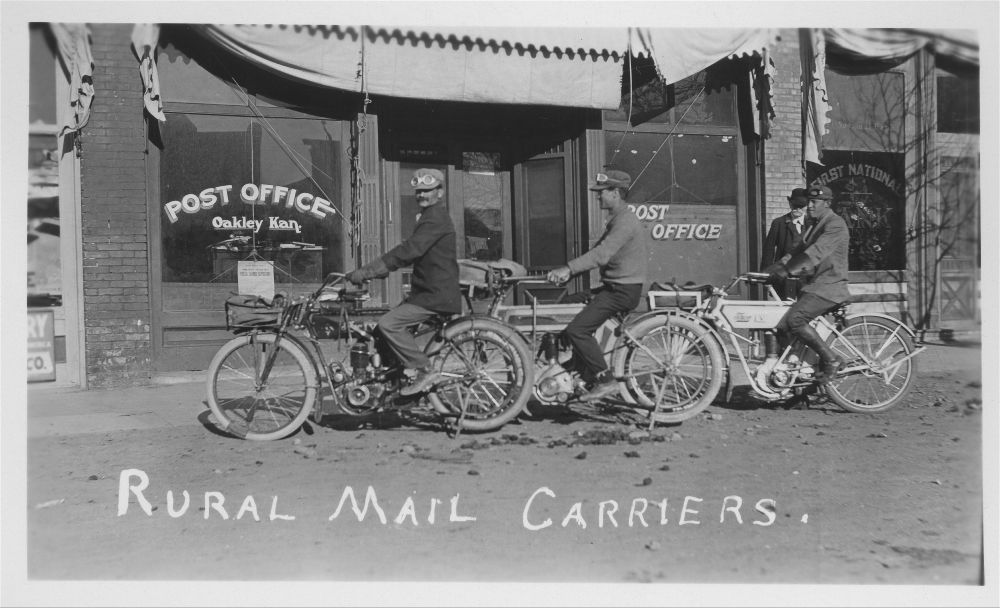 Photo of three rural mail carriers on their motorcycles in front of the post office at Oakley, between 1900 and 1919.