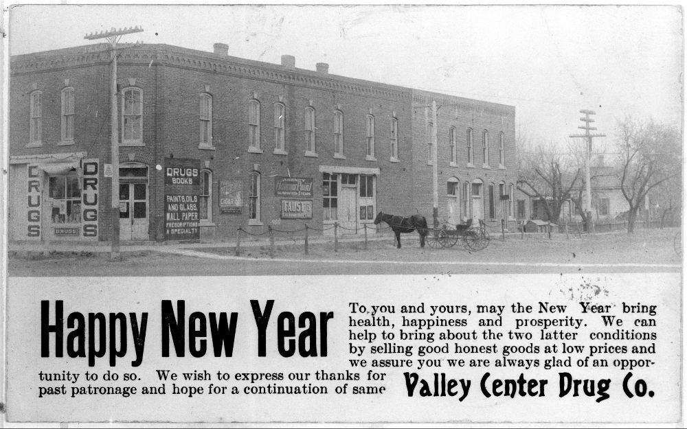 Photograph of a New Year's greeting card from drug store in Valley Center, 1907, including an exterior view of the building.