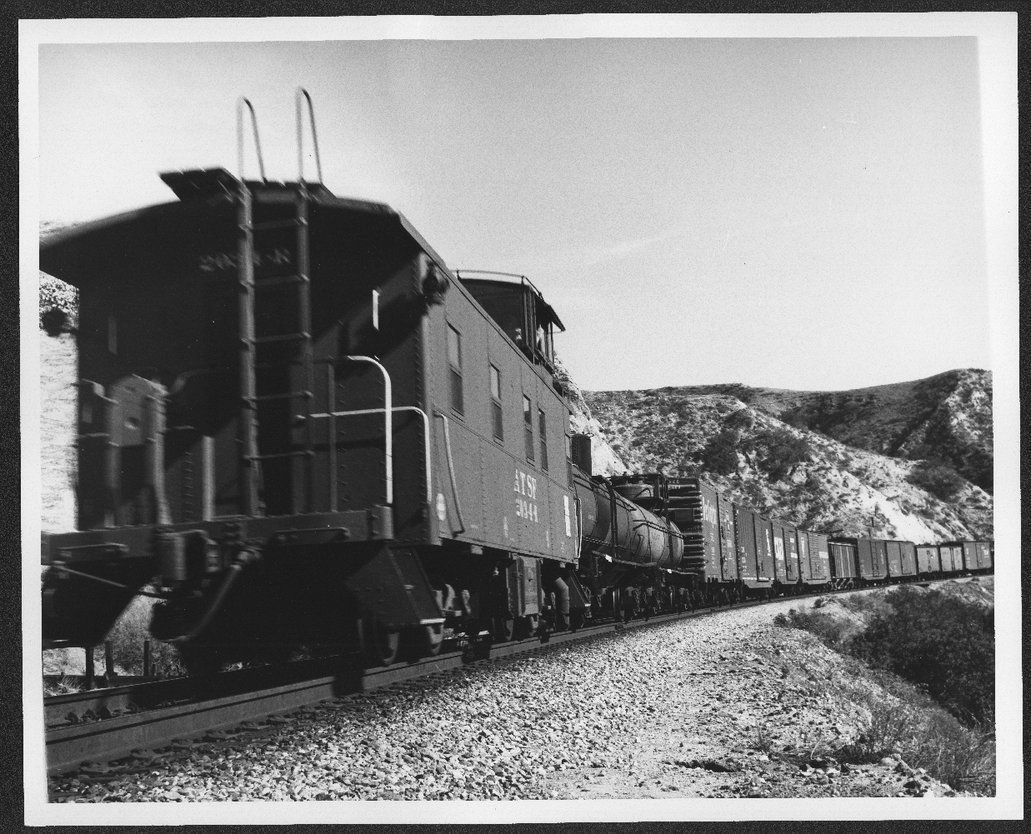Atchison Topeka & Santa Fe caboose 2034-R at the end of a manifest train in Cajon Pass, California.