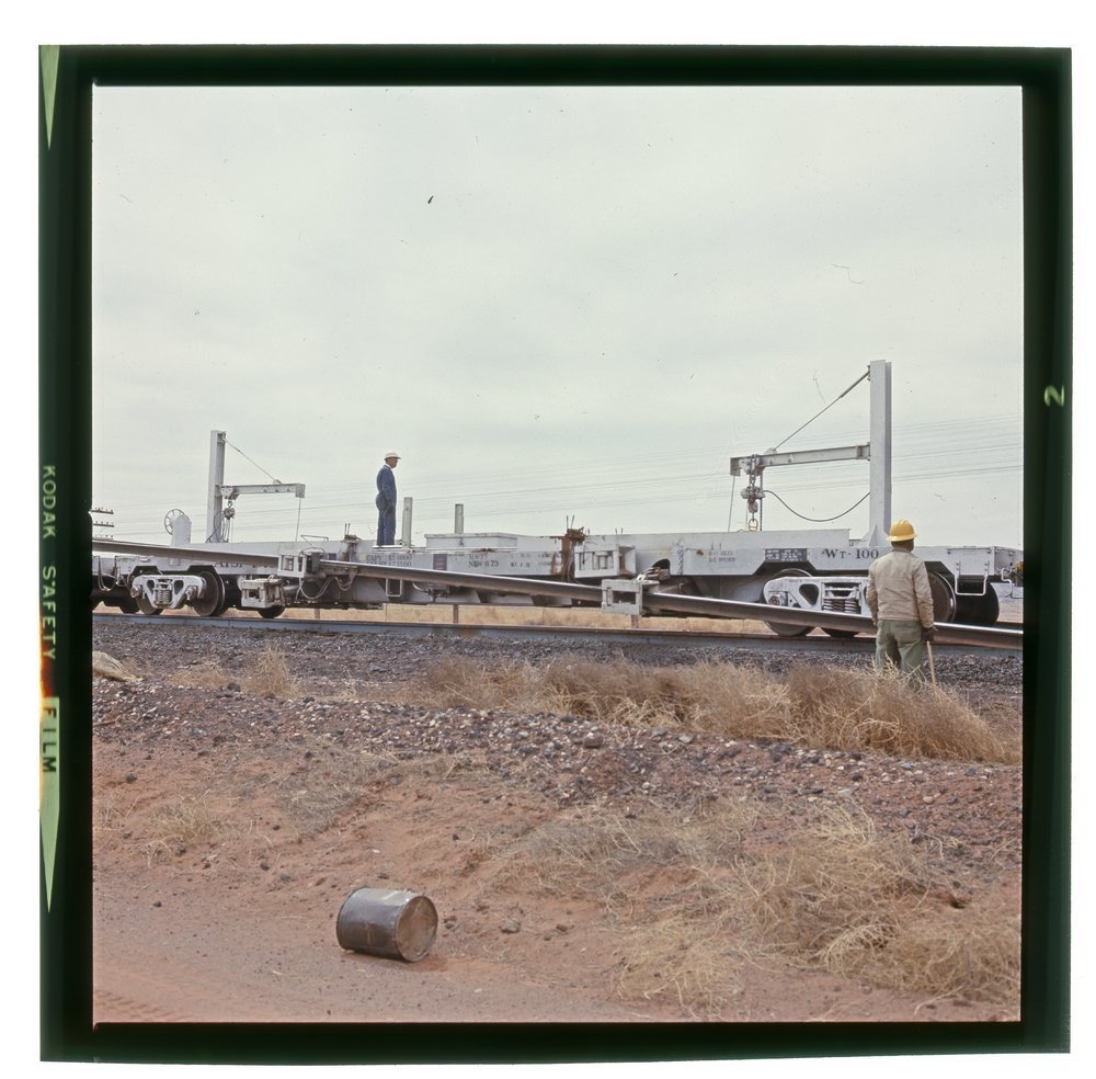 Atchion, Topeka & Santa Fe flat car unloading welded rail