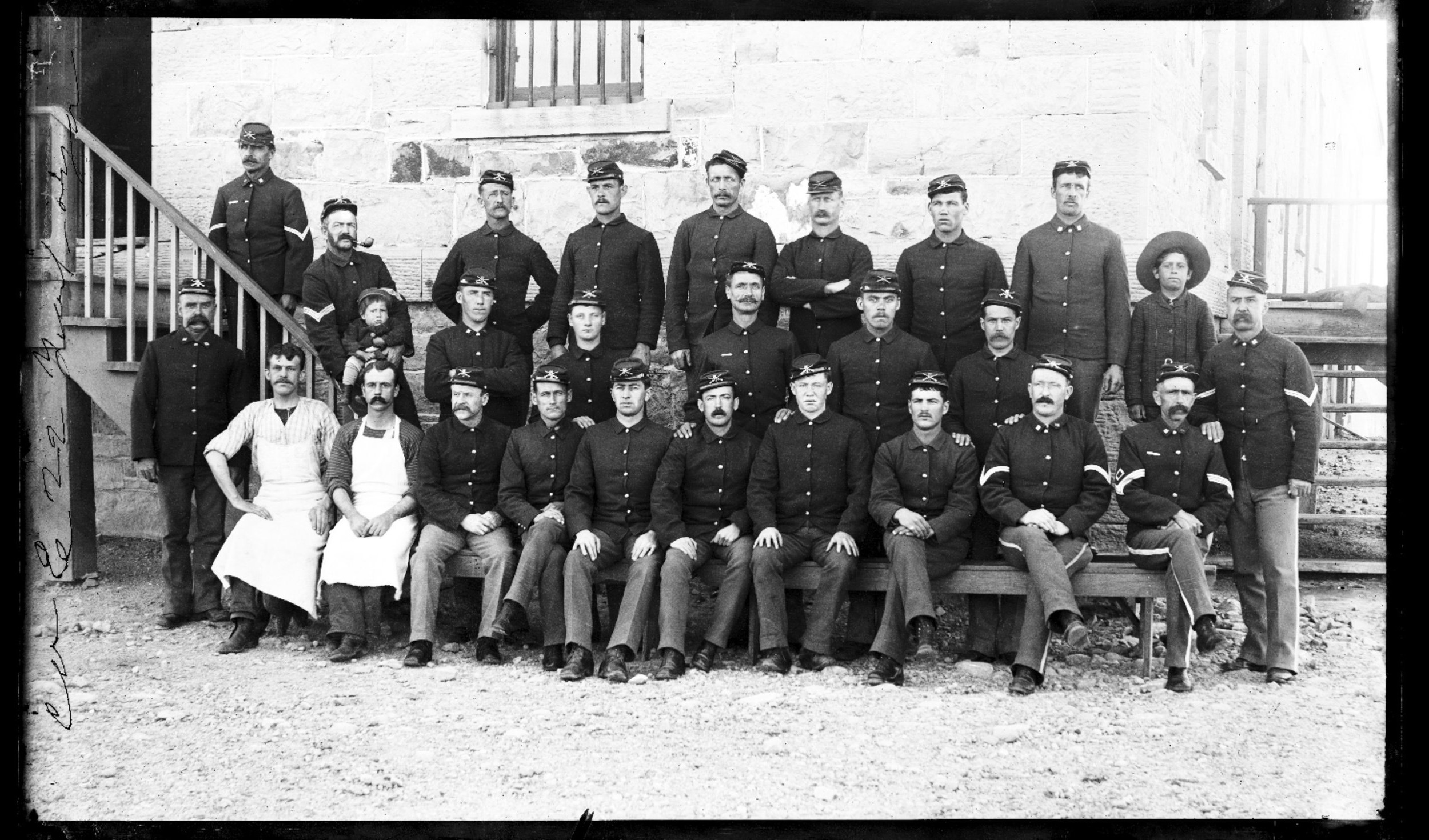 Fort Lyon and Fort Union - Company E, 10th Infantry, at Fort Lyon, Colorado. Soldiers are pictured seated in front of a building. Neg #4