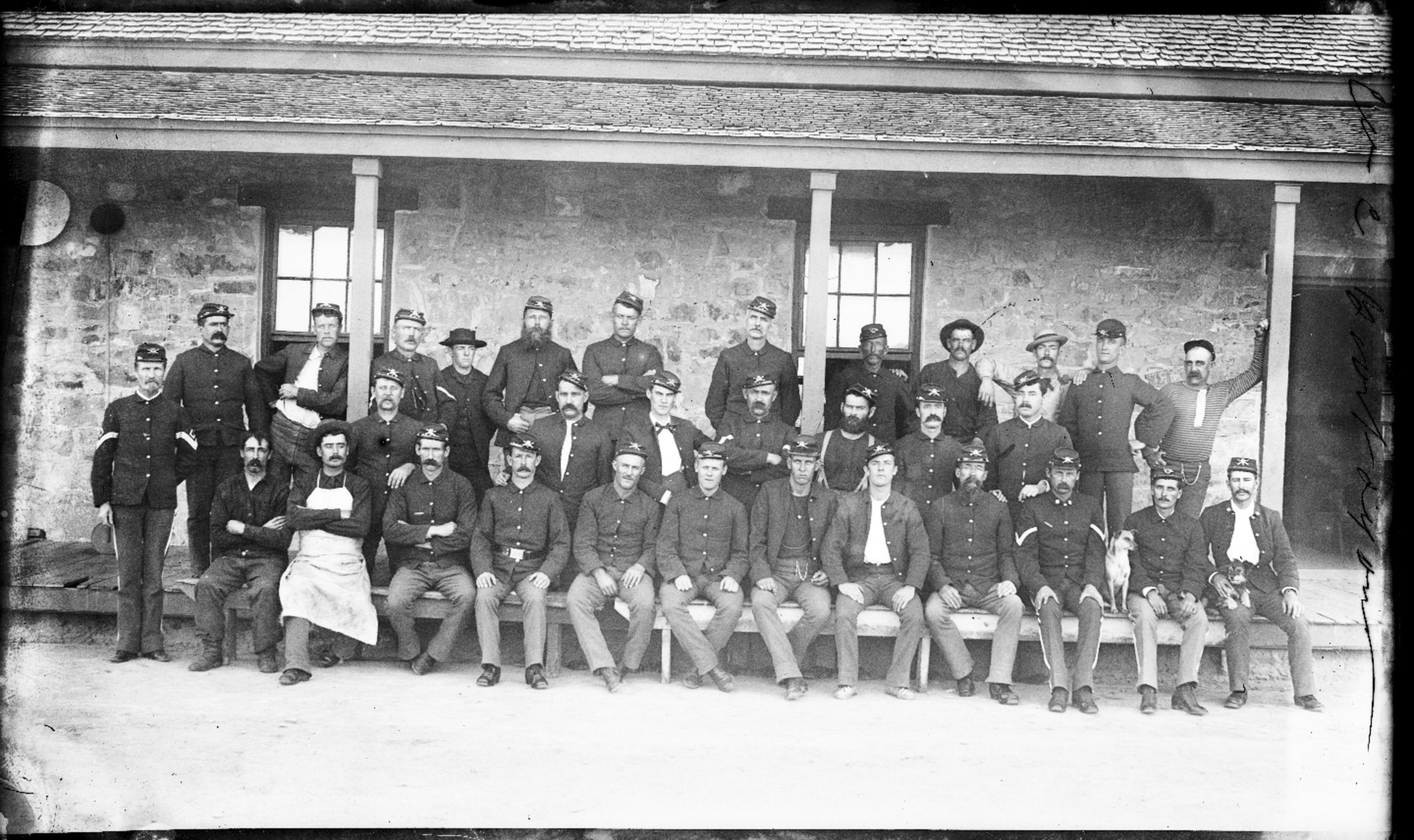 Fort Lyon and Fort Union - Company C, 22nd Inffantry at Fort Lyon, Colorado. Soldiers are pictured sitting in front of a builiding. 1st Sergent Horner is pictured at the far right.  Neg #5