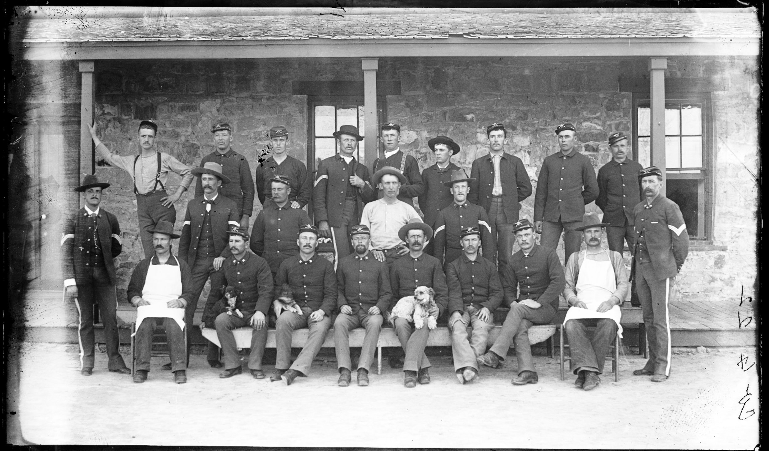 Fort Lyon and Fort Union - Company F, 22nd Infantry, Fort Lyon, Colorado. Soldiers are pictured in front of a building and many of them are holding dogs. Neg #8