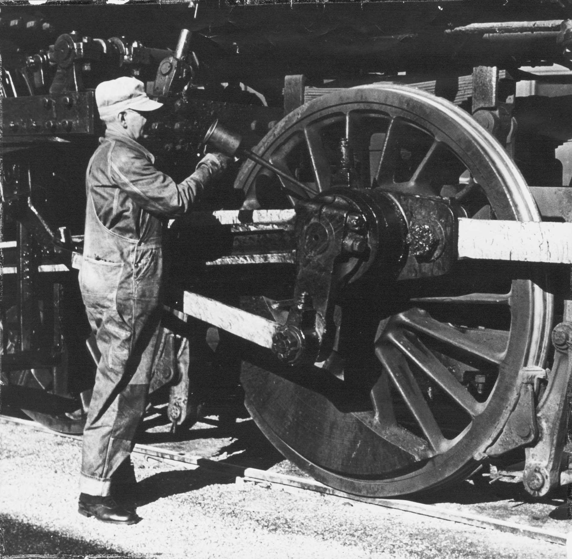 Harry D. Stewart oiling a locomotive wheel