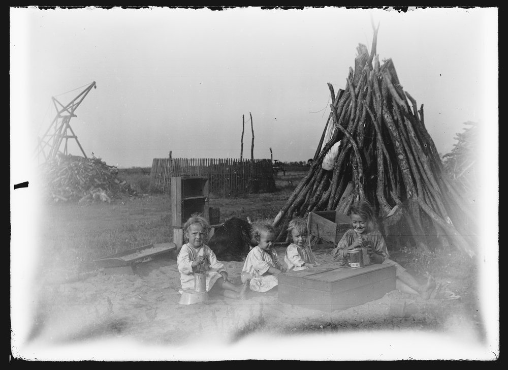 Golden Charles Dresher photograph collection - Four children, Florence, Dorothy, Donald, and Margaret Dresher, playing in a sand pile on the G.C. Dresher farm in McPherson County, Kansas in 1913-1914 (Neg. 2)