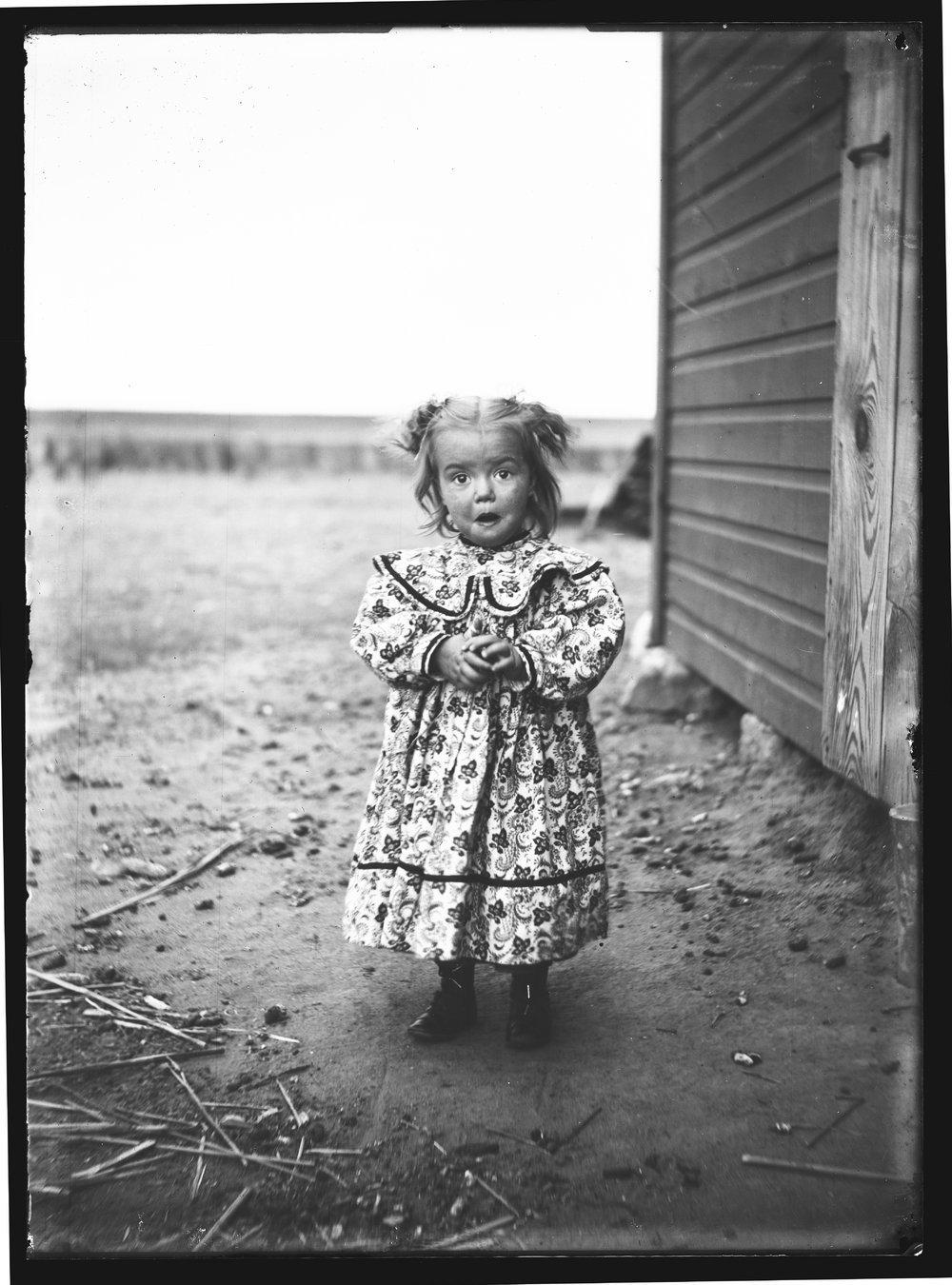 Golden Charles Dresher photograph collection - A little girl, Margaret Helen Dresher, standing outside of the G.C. Dresher farm in Finney County, Kansas in 1908 (Neg. 5)