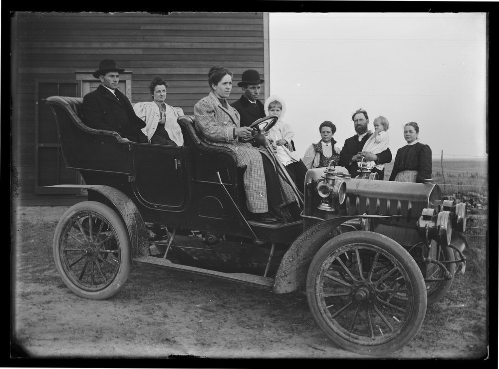 Golden Charles Dresher photograph collection - Two unidentified couples seated in Jess Brubaker's Mason automobile in Kansas about 1900.  Four of the Dresher family members are in the photo as well and they are located beside the car (Neg. 9)
