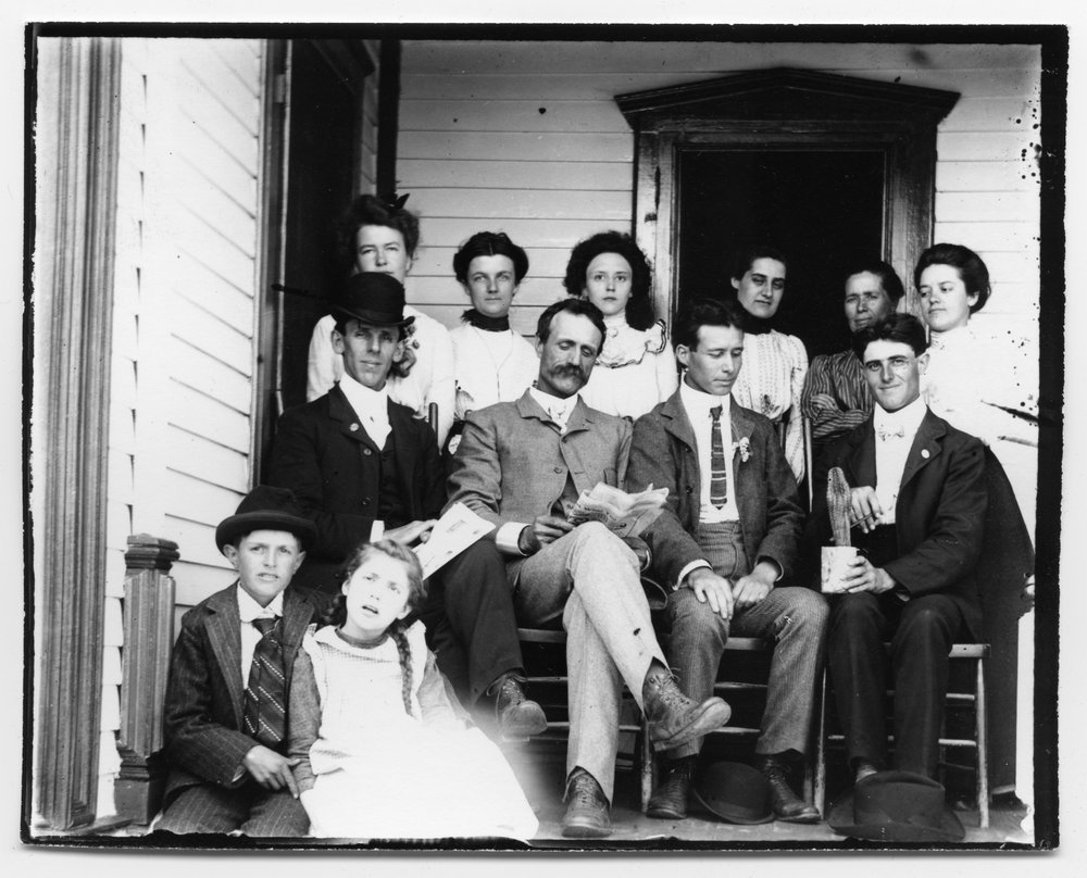 Golden Charles Dresher photograph collection - Group of men, women and children seated on the porch of the C.H. and Melissa Way's home near Canton, McPherson County, Kansas in 1902. (Neg. 12)