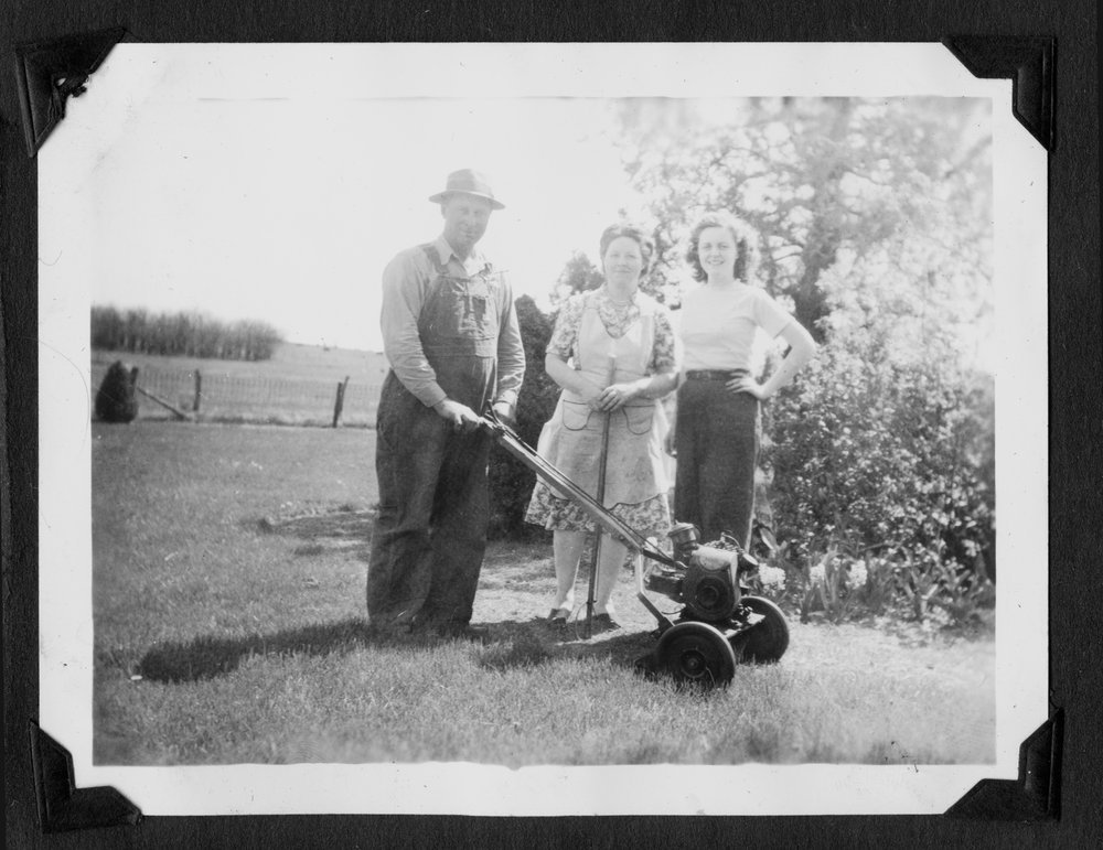 Melvin Brose photograph album - Carl,  Leona, and Charlene Brose on their farm near Valley Falls, Kansas, 1947.  Carl is using a lawnmower to cut the grass.