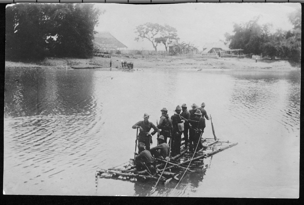 Crossing the Rio Grande de la Pampanga during the Philippine Insurrection - The first raft to cross the Rio Grande de la Pampanga is in the bushes, the second raft is on the bank and the third one is on the water.  Colonel Frederick Funston is on the bank at the far right.  He crossed the river on the first raft.  *179