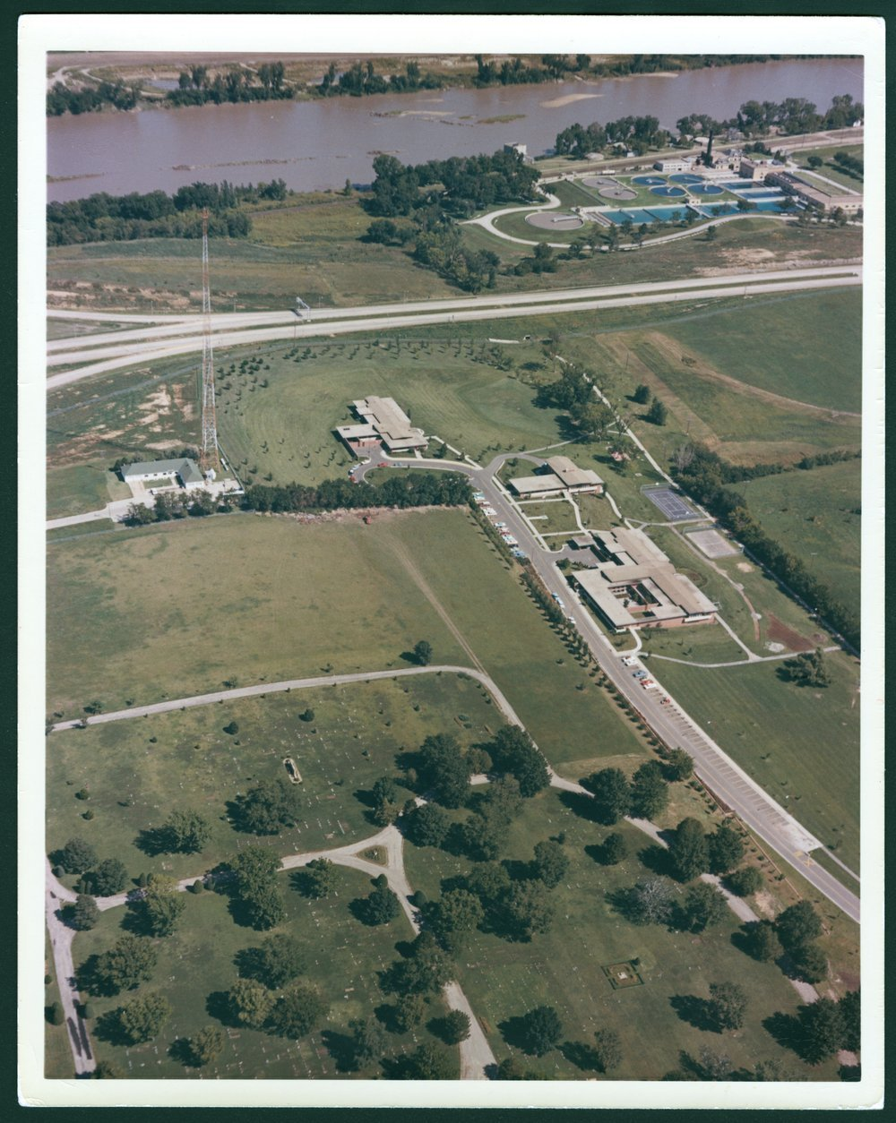 Aerial views of the Menninger Clinic Children's Division in Topeka, Kansas - This colored aerial photograph is facing north.  The Kansas river is in the background.