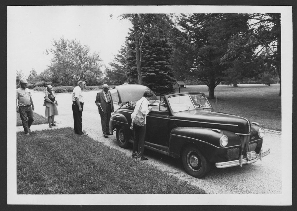 Karl Menninger, M.D. - This is a black and white photograph of Dr. Karl's little red Ford roadster, taken at the 1971 alumni reunion.  Dr. Karl is by the trunk and Homer Jameson is beside the car.