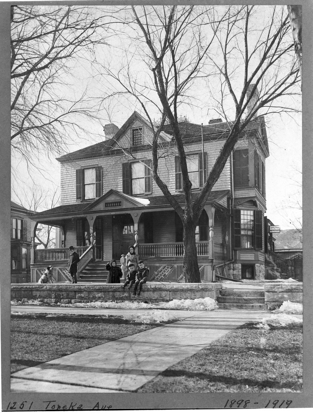 Charles F. Menninger homes in Topeka, Kansas - This is the C. F. Menninger family home  at 1251 Topeka Avenue in 1901.  Karl, Edwin and Will are seated on the wall.  William R. Kircher is standing on the left.  The St. Bernard dog is Guard.