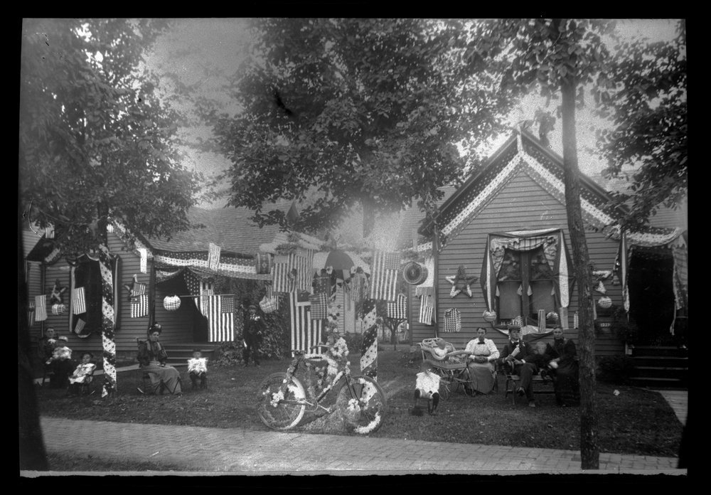 Charles F. Menninger homes in Topeka, Kansas - This is the C. F. Menninger family home  at 1270 Topeka Avenue decorated for the Fourth of July, 1898. Karl is in the chair and Edwin in the baby buggy with Flo nearly.