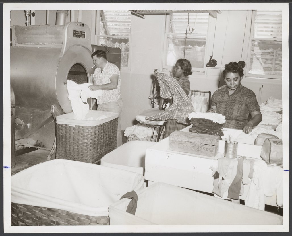 The laundry at the Menninger Clinic, Topeka, Kansas - Edward Hanshaw unloads laundry from the tumble-drier.  Ida Patterson sorts the patient's clothing.  Shirley Wright is ironing the clothing.