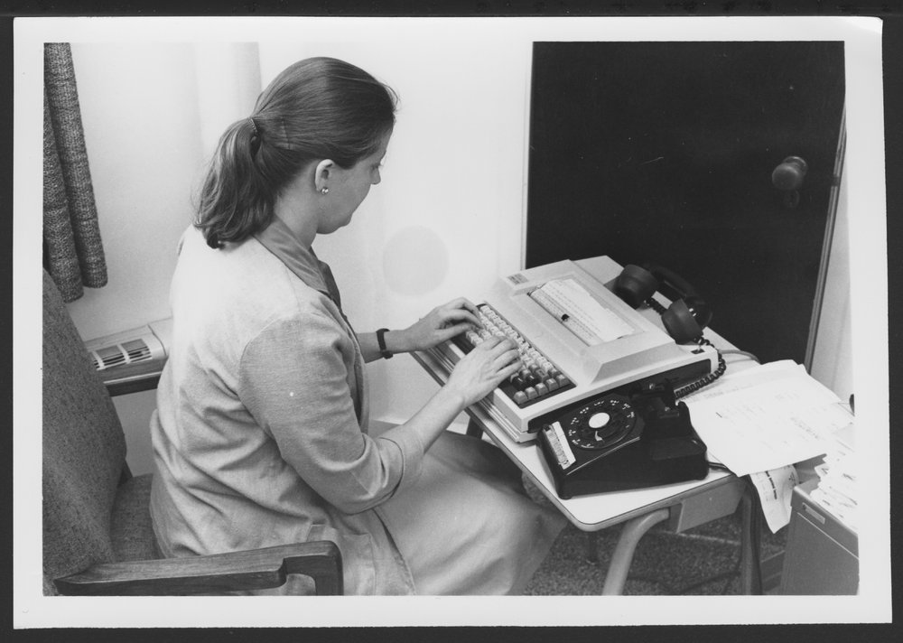 Menninger Foundation Professional Library, Topeka, Kansas - Alice Brand, Chief Librarian, is performing an early database search for information.  The computer modem worked only through the telephone receiver.