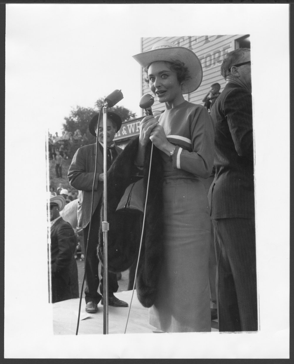 'Gunsmoke' cast members at a Kansas Centennial event - An unidentified woman at the microphone with Milburn Stone in the background.  The photograph was taken on Front Street in Dodge City, Kansas.