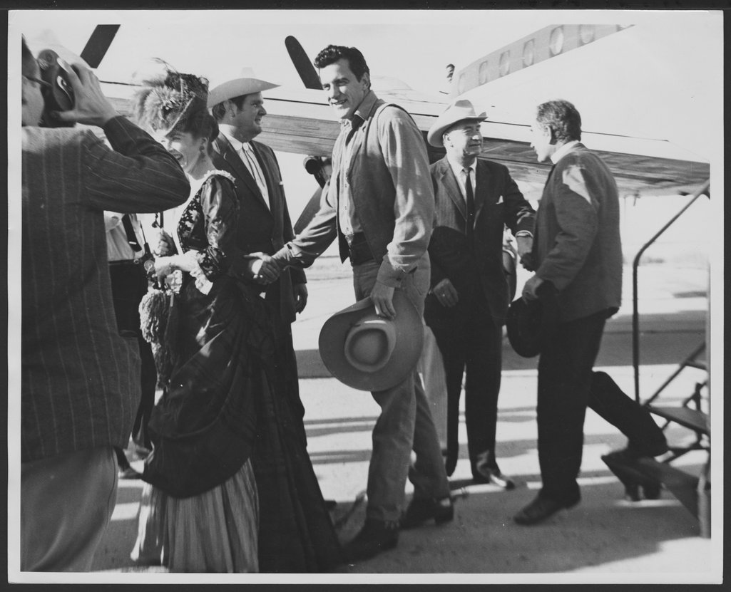 'Gunsmoke' cast members at a Kansas Centennial event - Amanda Blake, James Arness, and Milburn Stone deplane at an unidentified airport.  Chill Wills greets Milburn Stone as he steps off the stairs. *162