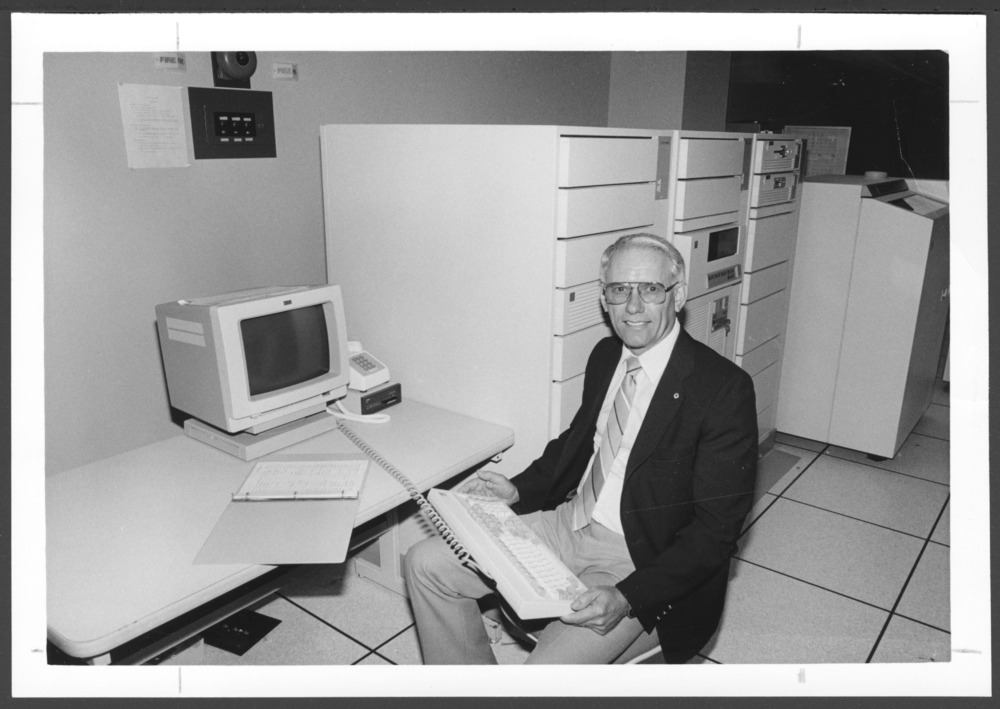 Menninger photograph collection - View of Harold Winsinger with IBM AS/400 host computer.  Envelope #2729