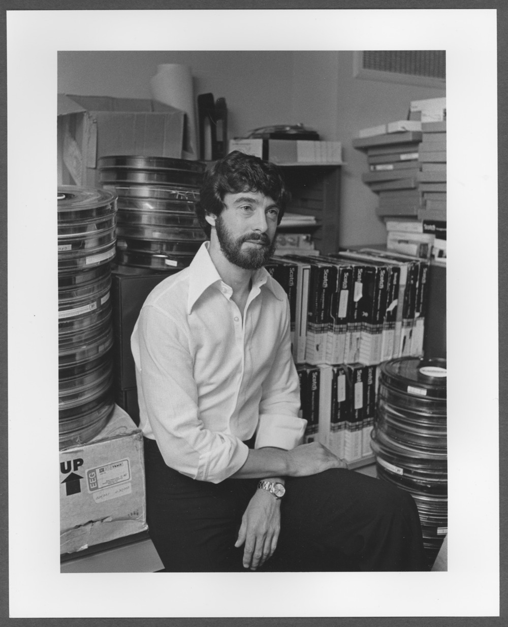 Menninger photograph collection - A man with with either computer or reel to reel recording tapes.  Envelope 688