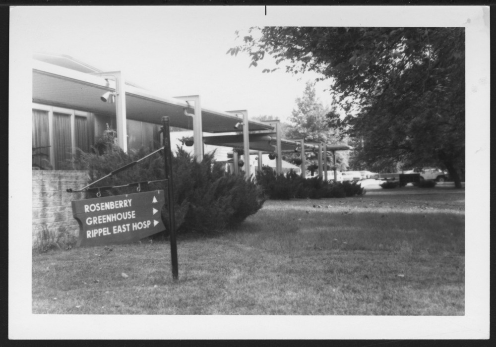 Menninger photograph collection - A photograph of a directional sign in front of a building c.1979.  Envelope 433