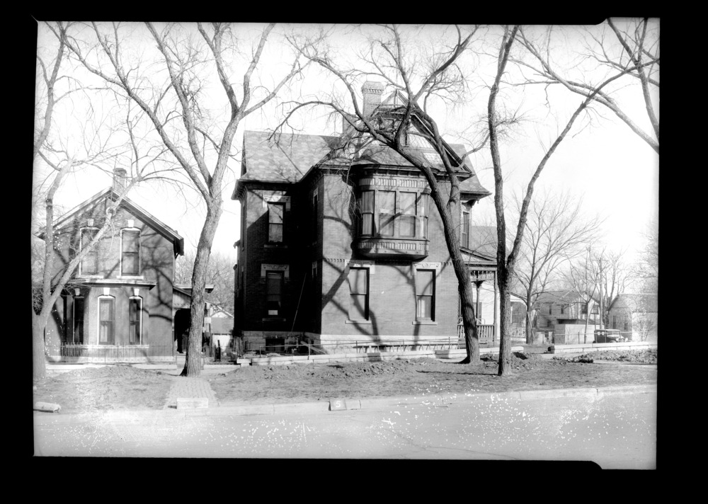 Homes and businesses in the area near the future site of the Topeka Boulevard bridge in Topeka, Kansas - This photograph shows a side view of the Victorian style duplex located at 132 2nd Street.  The photograph was taken on April 6, 1935. *5