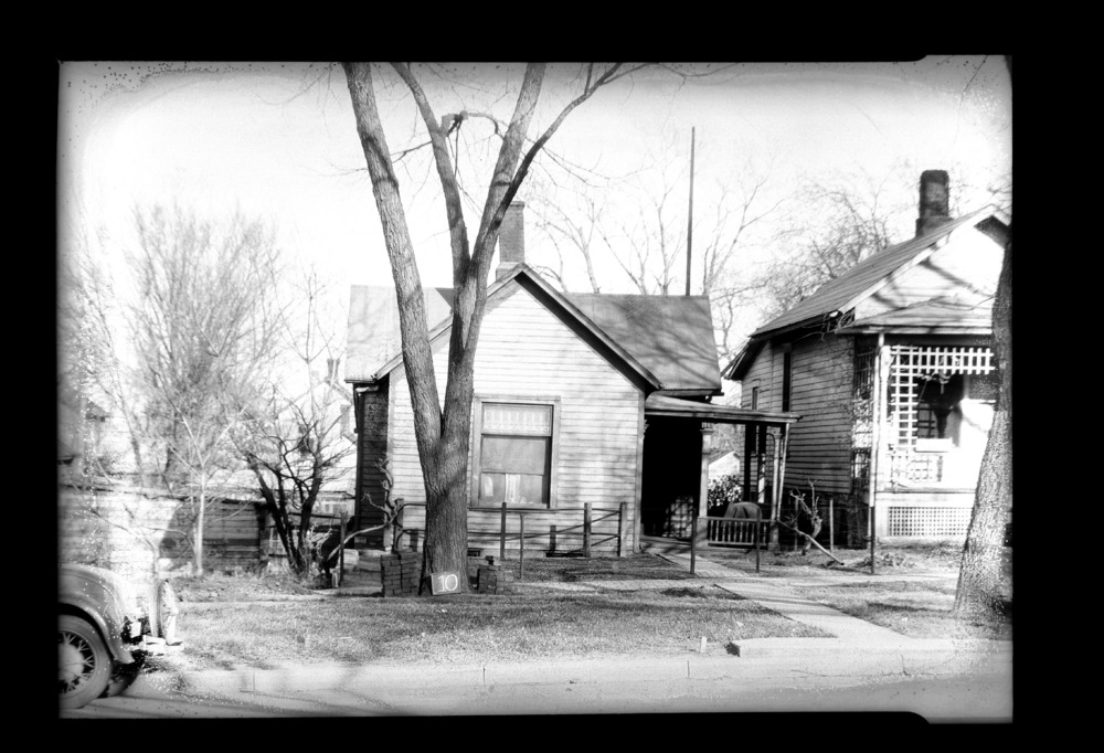 Homes and businesses in the area near the future site of the Topeka Boulevard bridge in Topeka, Kansas - This photograph shows a small house owned by Mrs. Anna L. Geiss  located 118 Topeka Boulevard.  The photograph was taken on April 6, 1935. *10