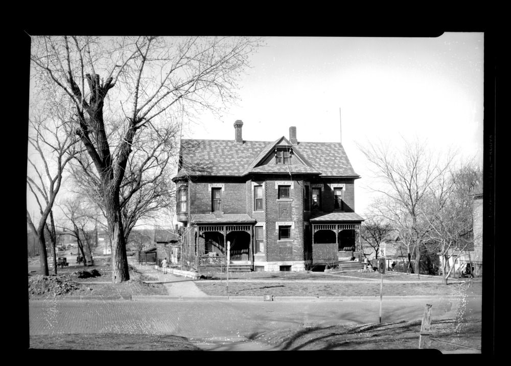 Homes and businesses in the area near the future site of the Topeka Boulevard bridge in Topeka, Kansas - This photograph taken on April 6, 1935 shows a Victorian style duplex on the south side of the river.  Notice the intricate details on the home, including the honeycomb like shingles and the detailed cement blocks over each window.  *3