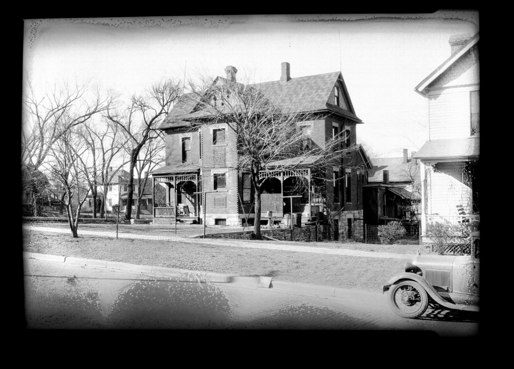 Homes and businesses in the area near the future site of the Topeka Boulevard bridge in Topeka, Kansas - This photograph shows a different angle of the Victorian style duplex.  Visible is an automobile, similar to a 1930's GM or Ford, though make or year is unable to be confirmed.  This photograph was taken on April 6, 1935. *4