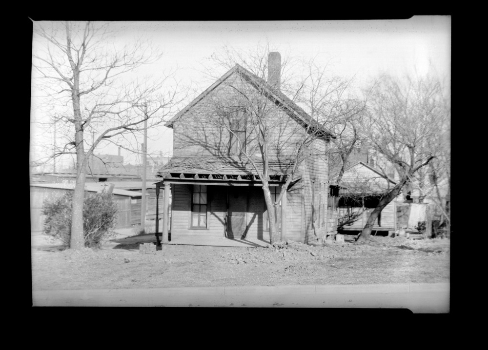 Homes and businesses in the area near the future site of the Topeka Boulevard bridge in Topeka, Kansas - This photograph shows a house owned by Ms. Mamie Johnson located at 114 Topeka Boulevard.  The photograph was taken on April 6. 1935. *11