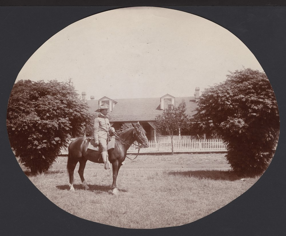 Soldier on a horse in front of an unidentified house possibly in Seward County, Kansas