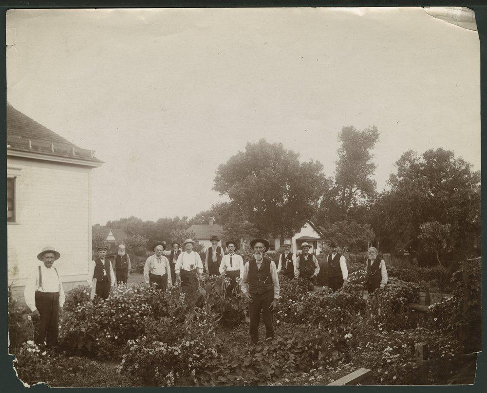 Men standing in a flower garden in Liberal, Kansas