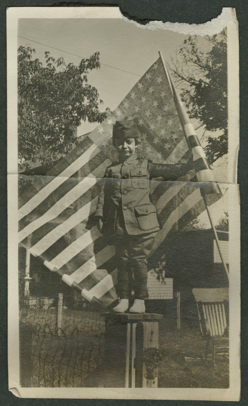 Child wearing a World War I uniform and holding a flag in Kinsley, Kansas