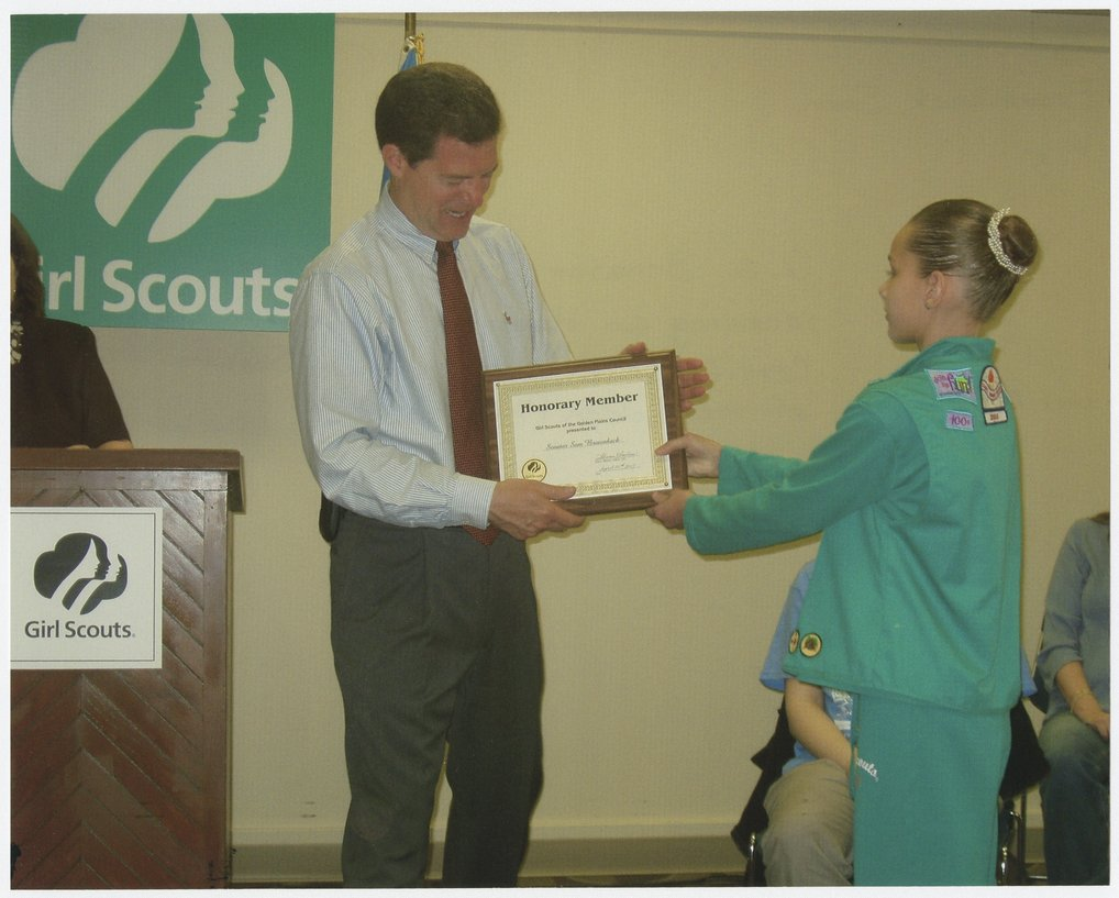 Senator Sam Brownback accepting a certificate from the Girl Scouts