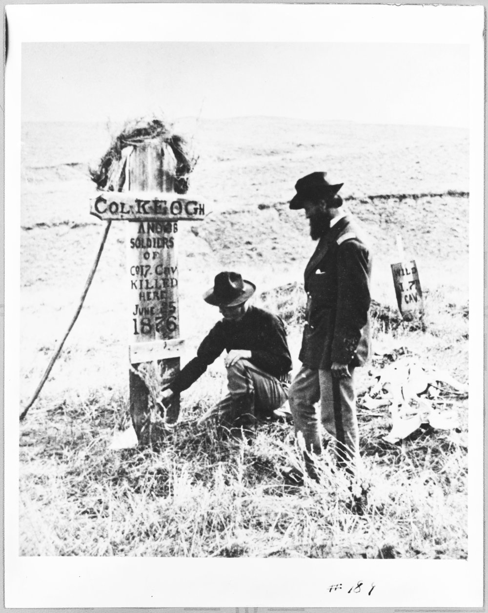 Two soldiers placing flowers on the grave of Colonel Keogh