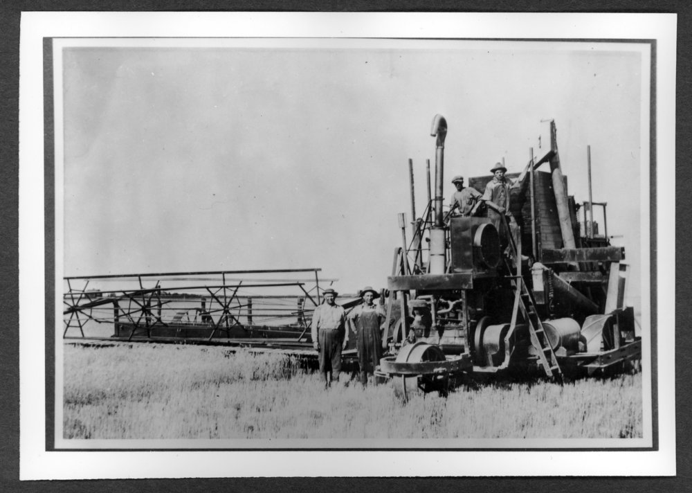 Scenes of Sherman County, Kansas - First machine powered combine in Sherman County.  Left to right are owner Henry Neu, Bill Baker, Floyd Beckner, and Ed Patterson.