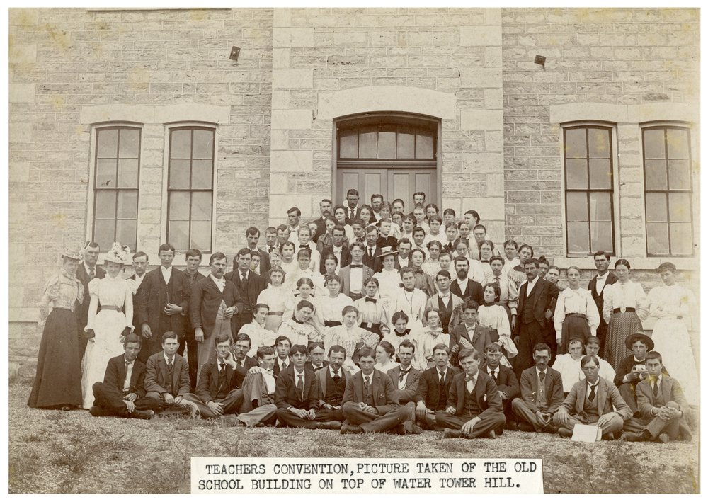 Gus Meier photograph collection - Attendees to a teacher's convention pose outside the old Alma high school.