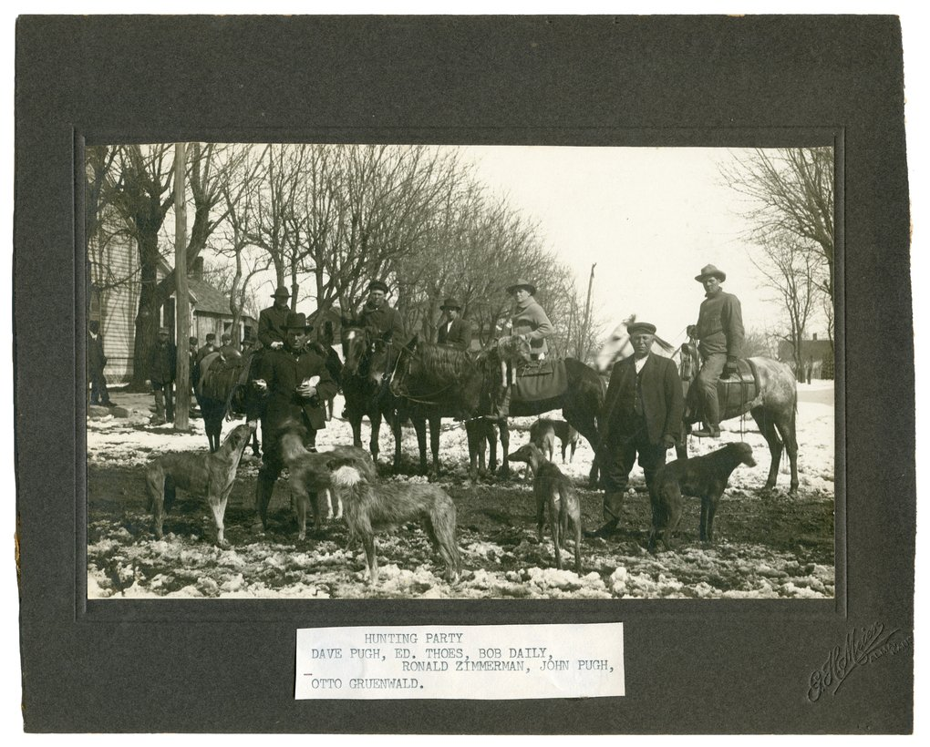 Gus Meier photograph collection - Group of men on horseback with their greyhound dogs after a coyote hunt.