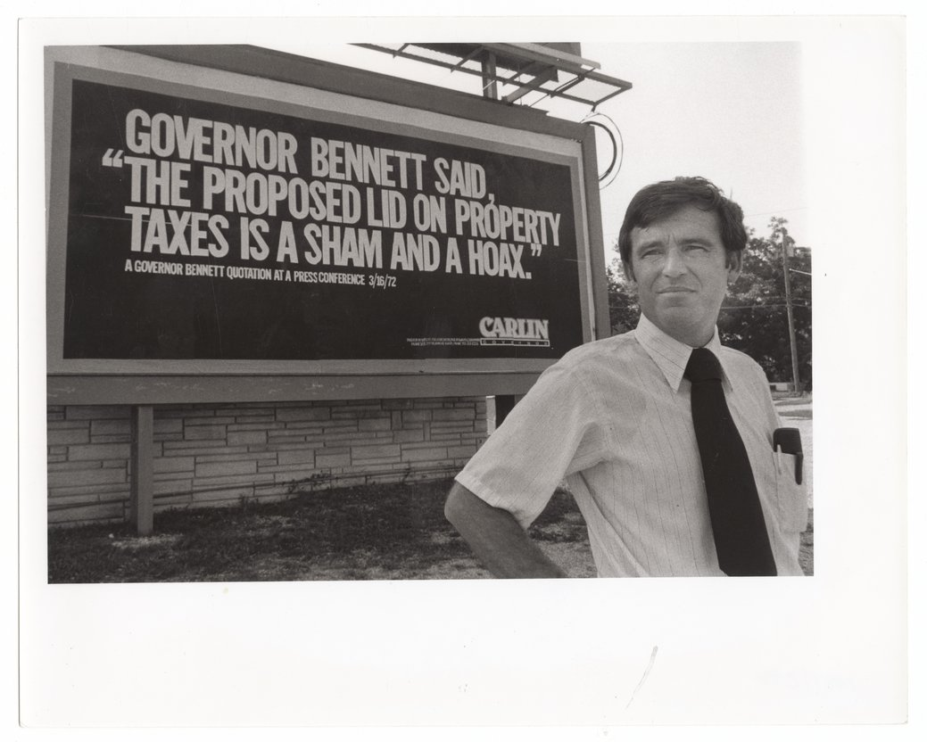 John William Carlin standing front of a campaign sign