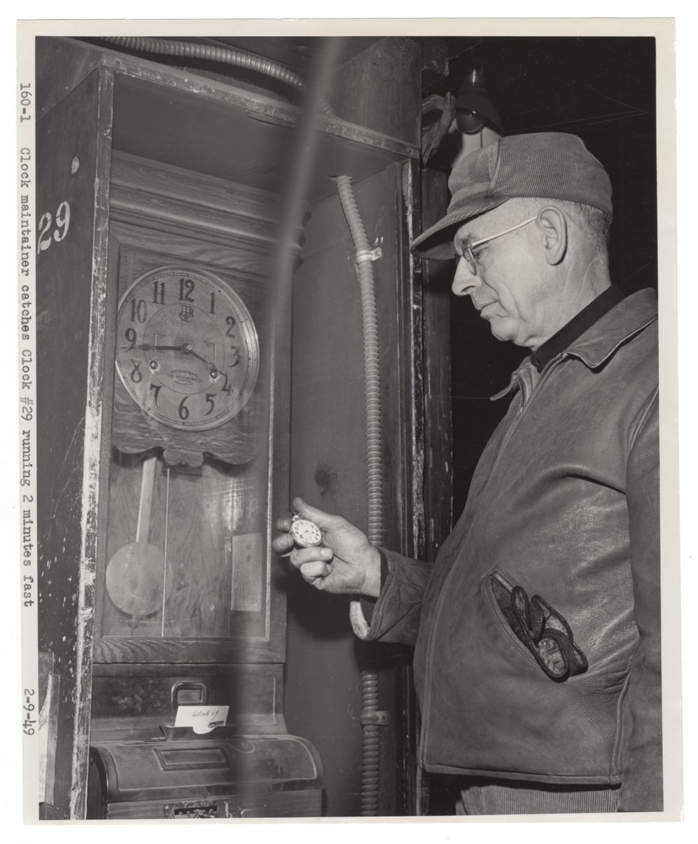 Atchison, Topeka & Santa Fe Railway's clock maintainer checking a clock - 1