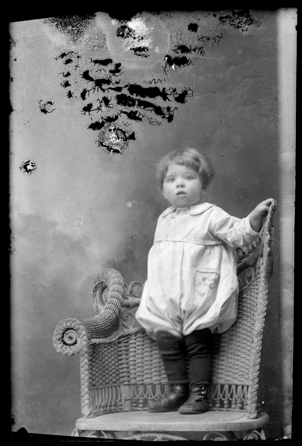 Michael A. Kennedy photo collection, St. Paul, Kansas - Portrait of young child standing on wicker chair (slide 2746, 2747)