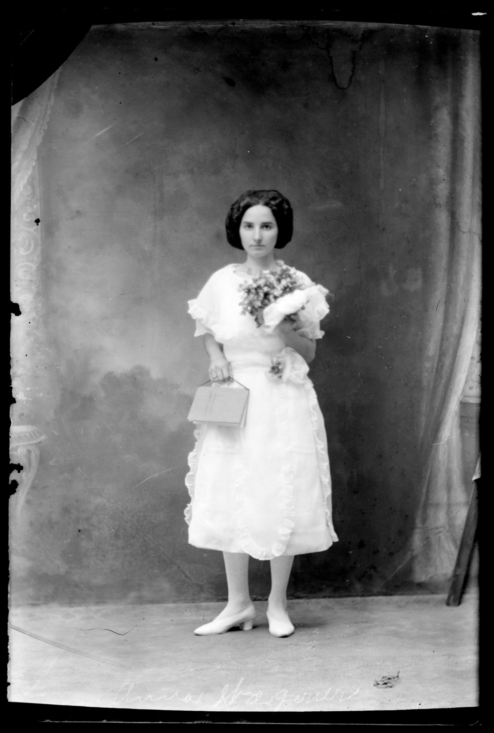 Michael A. Kennedy photo collection, St. Paul, Kansas - Portrait of Anna (Wagner) Kennedy in a white dress holding flowers and a handbag (2747)