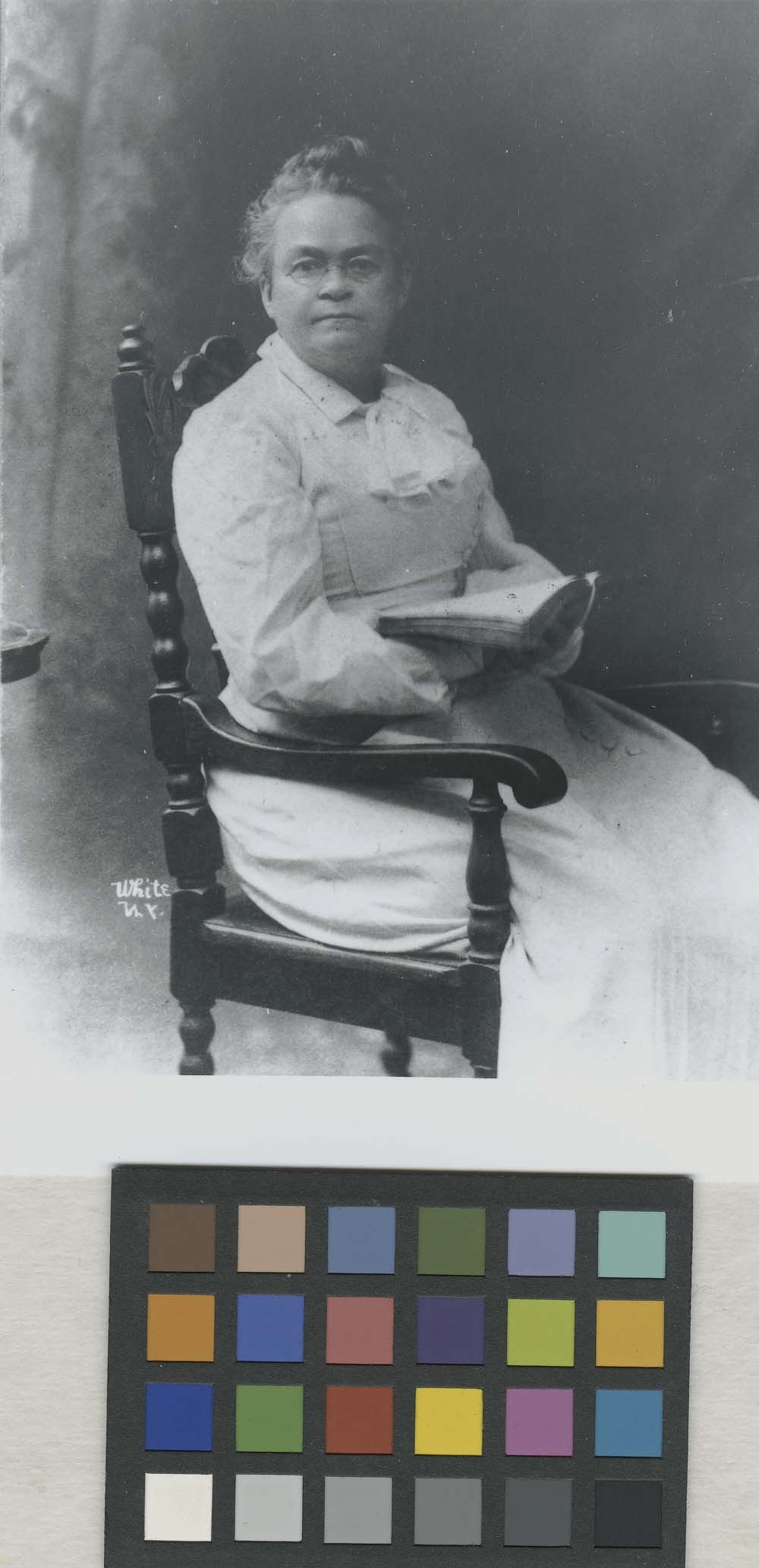 Carry Amelia Nation seated in a chair holding a book