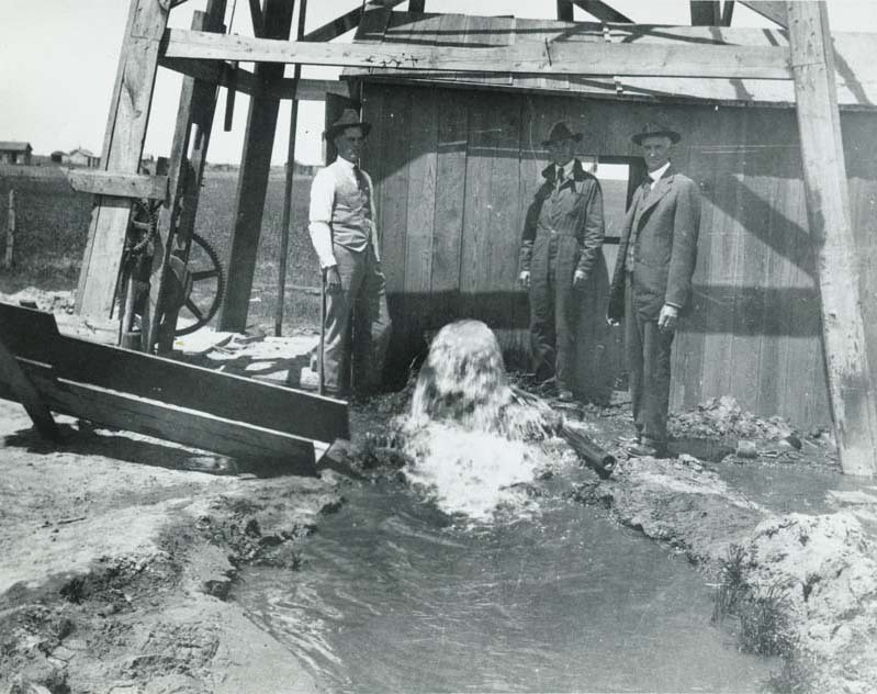 Three men at a pump house and irrigation ditch