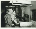 Cooks preparing a meal in a kitchen car on an Atchison, Topeka & Santa Fe Railway troop train