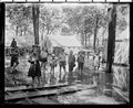 Chautauqua in Forest Park, Ottawa - A gathering of children enjoying wading while their families attended the Chautauqua in Forest Park, Ottawa.  Note wood furniture outside of tent.