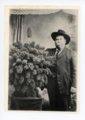 Man poses with large bunch of kaffir corn, El Dorado, Butler County, Kansas - front