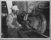 Atchison, Topeka & Santa Fe employee oiling a freight car, Argentine, Kansas