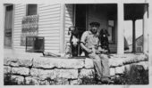 Young man sitting on a porch with two dogs